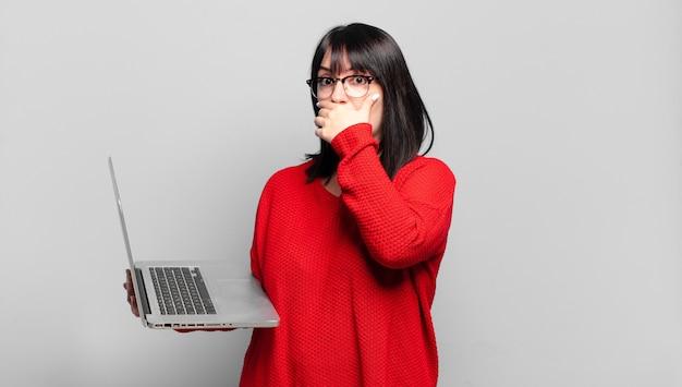 Jolie femme taille plus couvrant la bouche avec les mains avec une expression choquée et surprise, gardant un secret ou disant oups