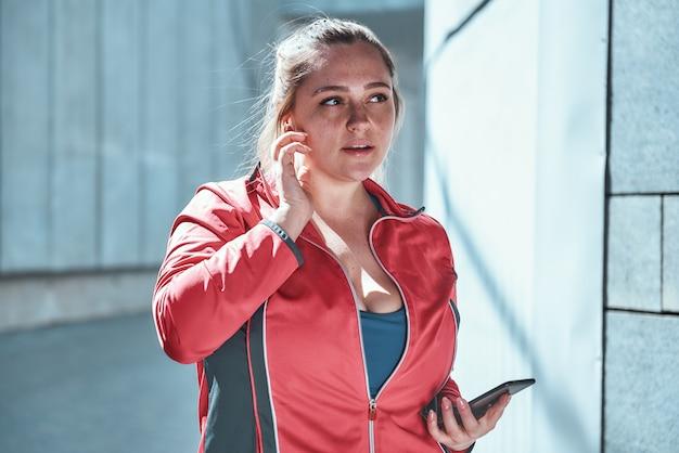 Jolie femme de taille plus dans des écouteurs tenant un téléphone intelligent et écoutant de la musique en se tenant debout