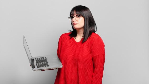 Jolie femme taille plus haussant les épaules, se sentant confuse et incertaine, doutant avec les bras croisés et le regard perplexe