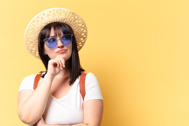 Jolie femme taille plus avec des lunettes de soleil et un chapeau en vacances