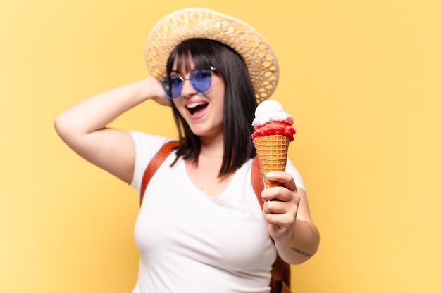 Jolie femme taille plus avec des lunettes de soleil, de la crème glacée et un chapeau en vacances