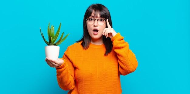 Jolie femme de taille plus semblant surprise, bouche bée, choquée, réalisant une nouvelle pensée, idée ou concept