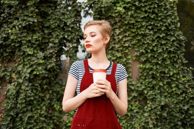 Jolie femme avec une tasse de boisson dans la rue près des buissons