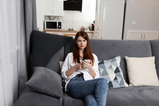 Jolie femme avec un téléphone dans ses mains assis à la maison dans une communication intérieure d'appartement.