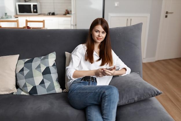 Jolie femme avec téléphone en mains loisirs de communication intérieure.