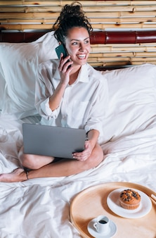 Jolie femme avec téléphone et ordinateur portable au lit