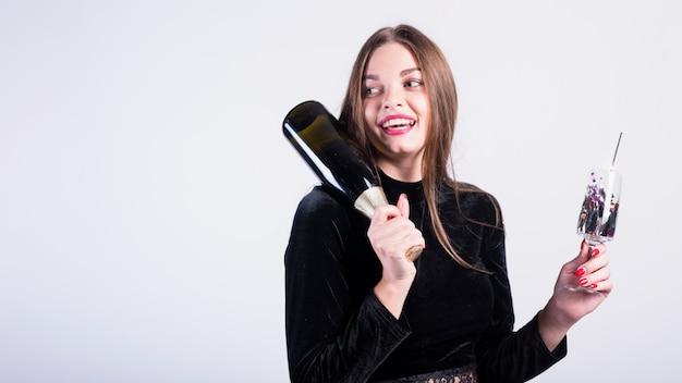 Jolie femme tenant une bouteille de champagne