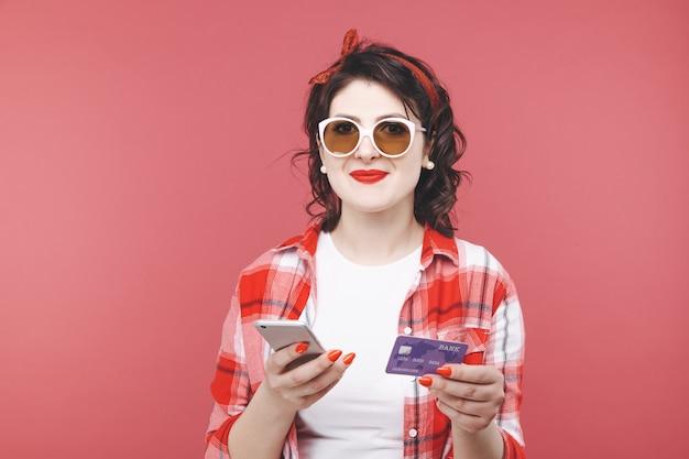 Jolie femme tenant une carte de crédit et un téléphone pour faire des achats en ligne.