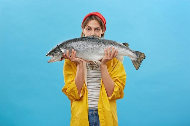 Jolie femme tenant d'énormes poissons