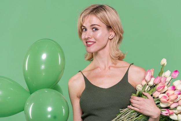 Jolie femme tenant des fleurs et des ballons