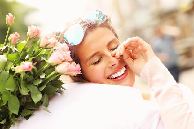Jolie femme tenant des fleurs et étreignant un homme