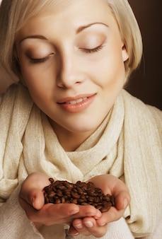 Jolie femme tenant des grains de café.