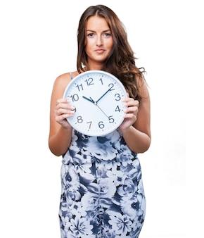 Jolie femme tenant une horloge