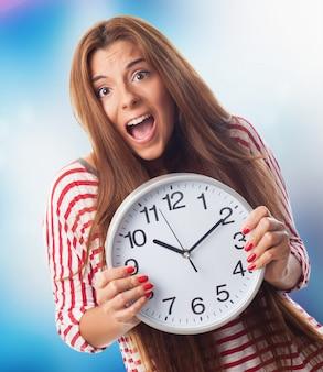 Jolie femme tenant horloge.