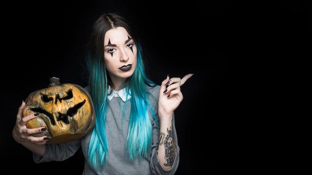 Jolie femme tenant jack-o-lantern effrayant