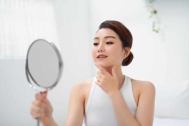 Jolie femme tenant un miroir et souriant à la caméra