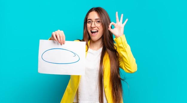 Jolie femme tenant un morceau vide d'espace de copie de papier