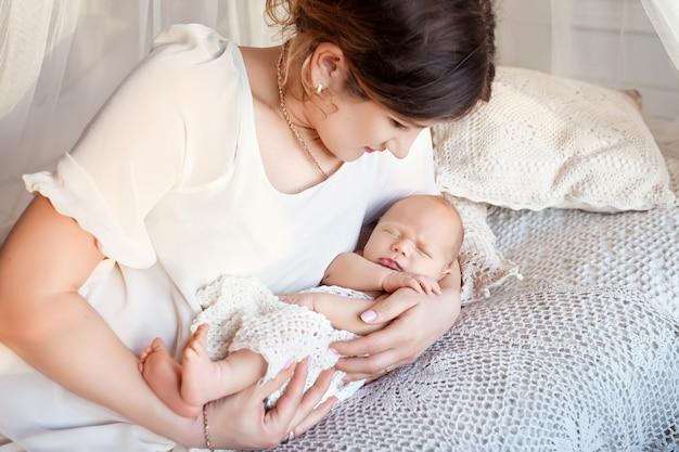 Jolie femme tenant un nouveau-né dans ses bras. heureuse mère et son bébé nouveau-né glissant dans le lit
