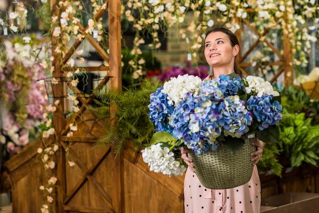 Jolie femme tenant un pot avec des fleurs dans la maison verte