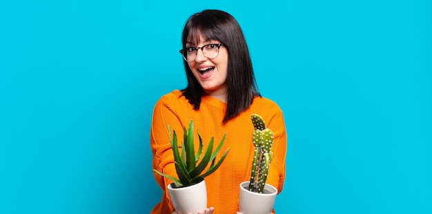 Jolie femme tenant des pots de cactus