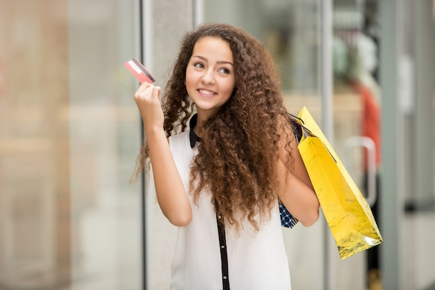 Jolie femme tenant des sacs à provisions et montrant une carte de crédit vierge