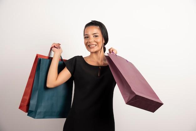 Jolie femme tenant des sacs à provisions sur mur blanc.