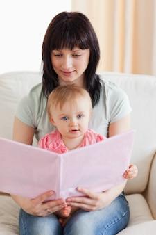 Jolie femme tenant son bébé et un livre dans ses bras assis sur un canapé