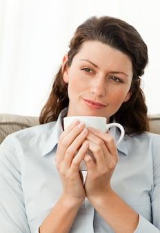 Jolie femme tenant une tasse de café, assis sur le canapé
