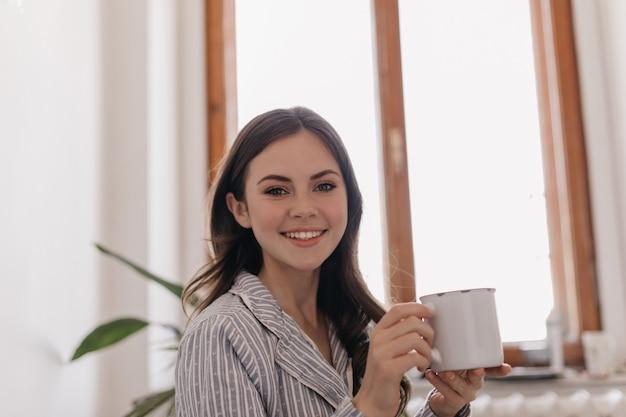 Jolie femme tenant une tasse de fer et regardant à l'avant avec le sourire