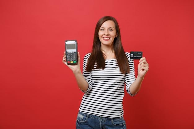 Jolie femme tenant un terminal de paiement bancaire moderne sans fil pour traiter et acquérir des paiements par carte de crédit carte noire isolée sur fond rouge. les gens émotions sincères mode de vie. maquette de l'espace de copie.