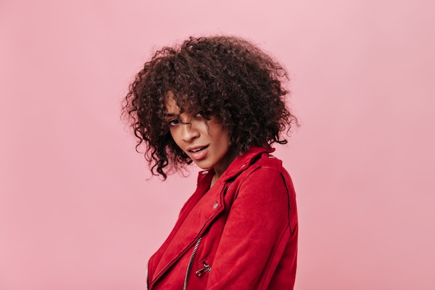 Jolie femme en tenue rouge regardant la caméra sur un mur isolé