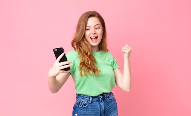 Jolie femme à tête rouge à l'aide de son téléphone intelligent