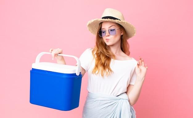 Jolie femme à tête rouge à l'air arrogante, réussie, positive et fière et tenant un réfrigérateur portable pique-nique