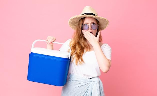 Jolie femme à tête rouge couvrant la bouche avec les mains avec un réfrigérateur portable choqué et tenant un pique-nique
