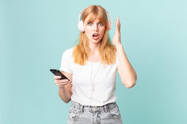 Jolie femme à tête rouge criant les mains en l'air et écoutant de la musique avec des écouteurs
