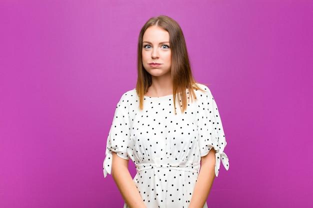 Jolie femme à tête rouge avec une expression maladroite, folle, surprise, les joues gonflées, se sentant bourrée, grasse et pleine de nourriture contre le mur violet