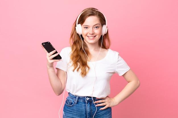 Jolie femme à tête rouge, heureuse et agréablement surprise avec des écouteurs et un smartphone
