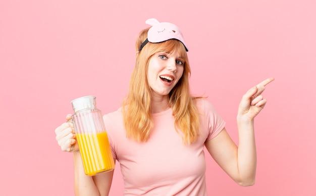 Jolie femme tête rouge en pyjama et tenant un jus d'orange. concept de petit déjeuner sain