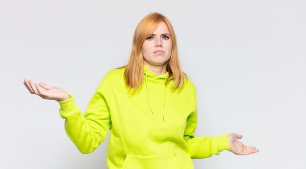 Jolie femme à tête rouge qui a l'air perplexe, confuse et stressée, se demandant entre différentes options, se sentant incertaine