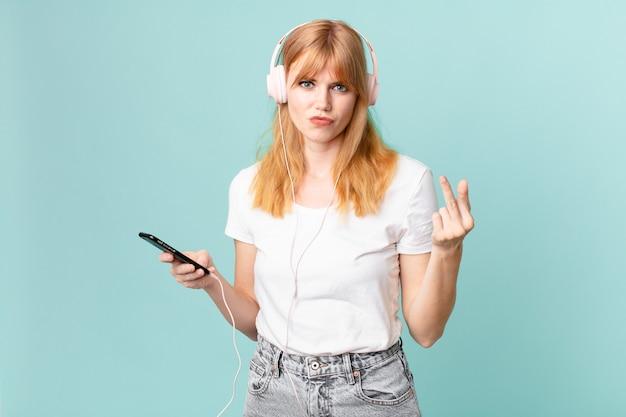 Jolie femme à tête rouge se sentant en colère, agacée, rebelle et agressive et écoutant de la musique avec des écouteurs