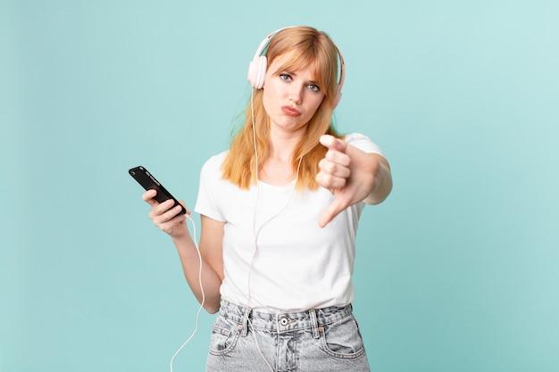 Jolie femme à tête rouge se sentant croisée, montrant les pouces vers le bas et écoutant de la musique avec des écouteurs