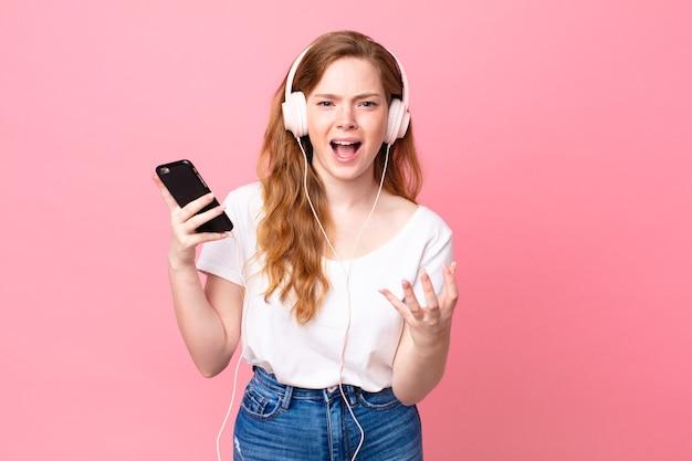 Jolie femme à tête rouge semblant en colère, agacée et frustrée par les écouteurs et le smartphone