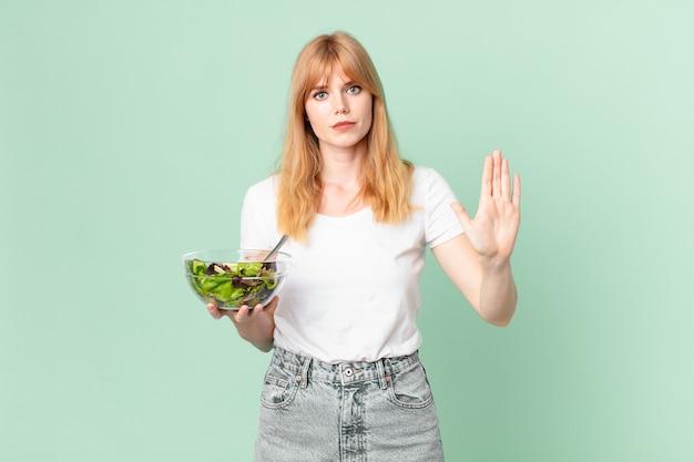 Jolie femme à tête rouge semblant sérieuse montrant la paume ouverte faisant un geste d'arrêt et tenant une salade. concept de régime