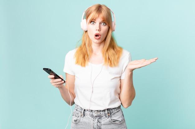 Jolie femme à tête rouge semblant surprise et choquée, avec la mâchoire tombée tenant un objet et écoutant de la musique avec des écouteurs