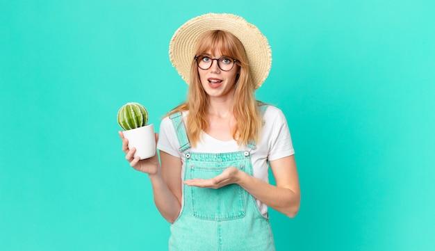 Jolie femme à tête rouge souriant joyeusement, se sentant heureuse et montrant un concept et tenant un cactus en pot. concept d'agriculteur