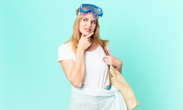 Jolie femme à tête rouge souriante avec une expression heureuse et confiante avec la main sur le menton avec des lunettes. concept d'été