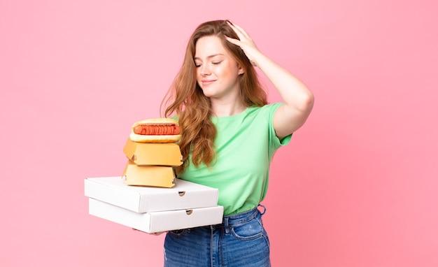 Jolie femme tête rouge tenant des boîtes de restauration rapide à emporter