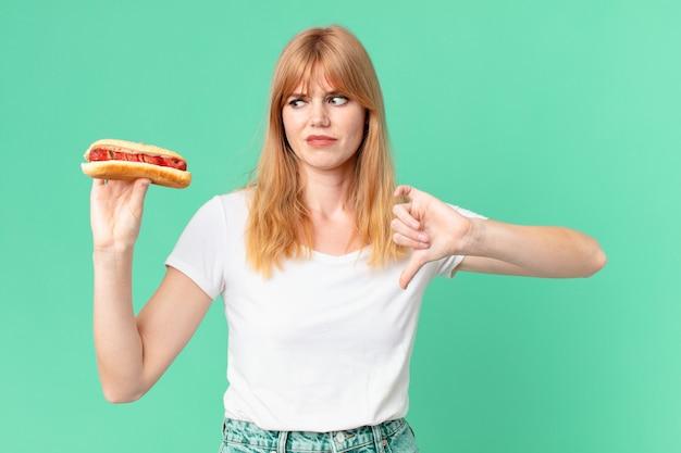 Jolie femme tête rouge tenant un hot-dog.