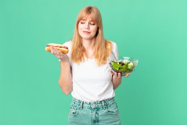 Jolie femme à tête rouge tenant une salade et un hot-dog. concept de régime