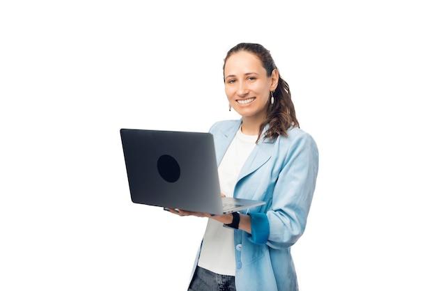 Jolie femme tient un ordinateur portable ouvert tout en souriant à la caméra.